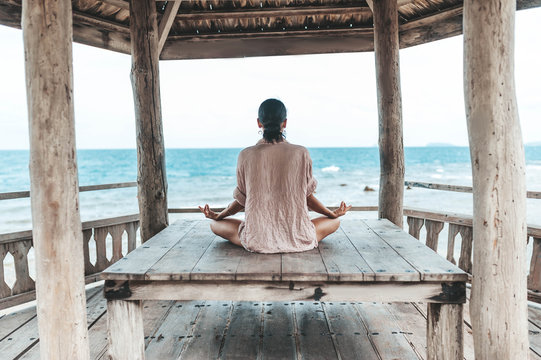young woman meditating in a yoga pose at the beach