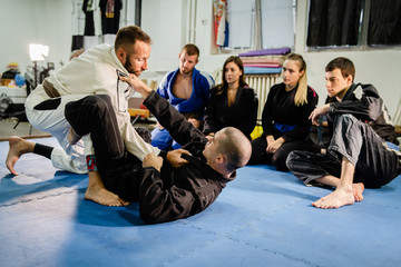 Brazilian Jiu JItsu BJJ professor teaching technique from the guard position to his students in training class at the martial arts academy