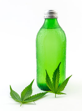 Green glass bottle with Cannabis CBD infused Water lemonade with cannabis leafs