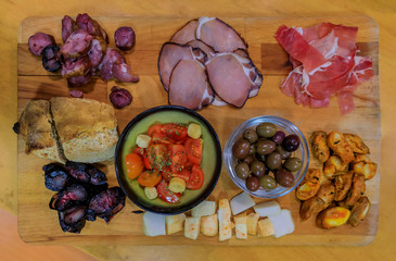 Board of traditional Portuguese food with blood and pork sausage, ham, bread, olives at a restaurant in Porto, Portugual