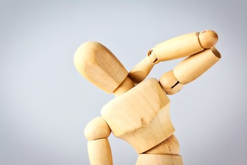 Wooden mannequin figure expressing neck pain.