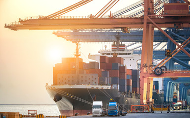 The cargo ship industry is parked in a harbor with a large crane bridge, transporting goods, importing and exporting trucks and airplanes.-image