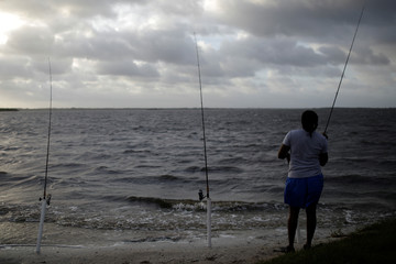A woman fishes in Indian River at Parrish Park ahead of the arrival of Hurricane Dorian in Titusville