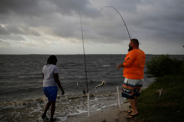 A man fishes in Indian River at Parrish Park ahead of the arrival of Hurricane Dorian in Titusville
