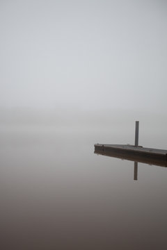 Empty boat dock on lake, on a foggy winter morning