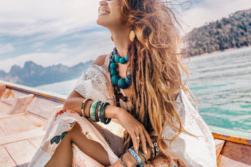 close up of fashionable young model in boho style dress on boat at the lake Wall mural