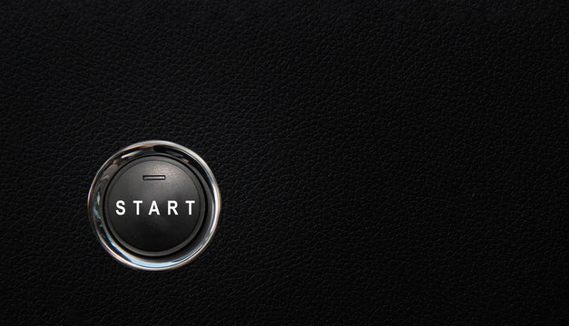Start button in a modern car, button on black textured surface