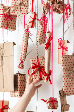 Handmade advent calendar hanging on a white wall. Child takes a gift, close up. Gifts wrapped in craft paper and tied with red threads and ribbons.