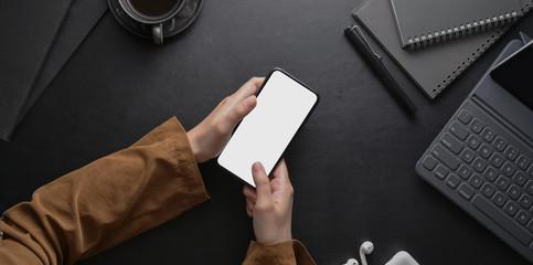 Female hand holding smartphone on dark stylish workplace