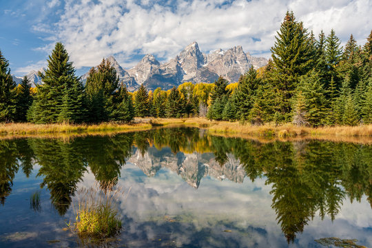 Landscape of mountains and trees of the Grand Teton range reflected in the ponds at Schwabacher Landing, Grand Teton National Park, Wyoming