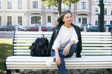 People, lifestyle, age, urban street style and fashion concept. Outdoor image of gorgeous attractive woman pensioner in trendy clothes waiting for friend on bench in park, enjoying nice sunny day