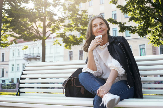 Low angle view of positive stylish middle aged female in trendy leather jacket, blue jeans and sneakers having pensive look, sitting comfortably on bench with cell phone, thinking where to have lunch