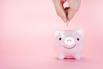 Hand putting coin in piggy bank on a pink background. Saving money concept.