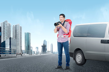 Asian man with a backpack holding a camera to take pictures