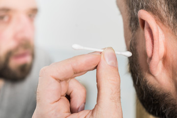 Man removing wax from ear using Q-tip