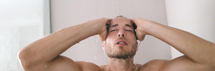 Shower bathroom in luxury hotel or home man taking hot bath washing hair under rainfall water banner panorama.
