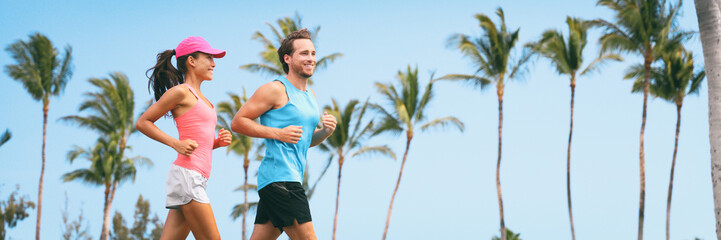 Fotobehang Palm boom Healthy people fit active lifestyle couple running on palm trees tropical background panoramic banner. Happy friends exercising together -training buddy friend.