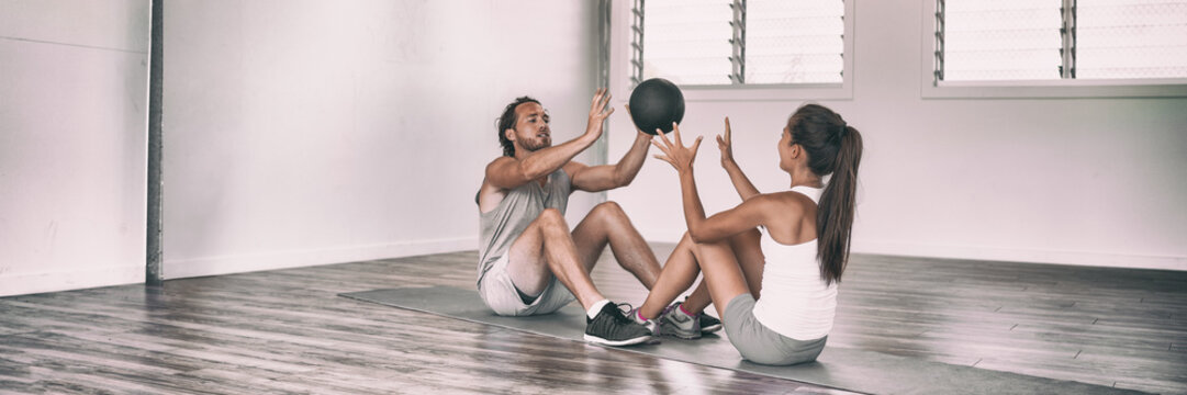 Gym fit medicine ball partner workout fun exercises friends training together in cross fitness class panoramic banner. Couple training body core workout throwing weighted slam ball at each other.