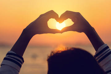 Beautiful Silhouette hand made heart shape on the sunset background