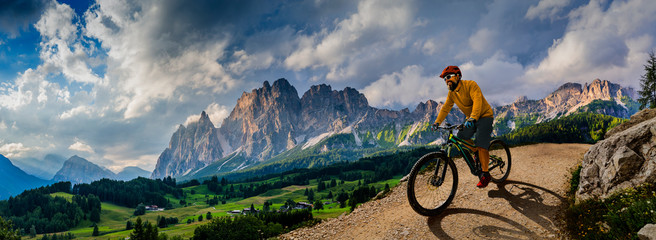 Man cycling on electric bike, rides mountain trail. Man riding on bike in Dolomites mountains landscape. Cycling e-mtb enduro trail track. Outdoor sport activity. Wall mural