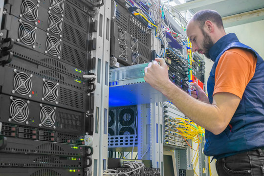 A man works in a server room. System administrator installs a new server in a modern data center. A technician repairs the central router.
