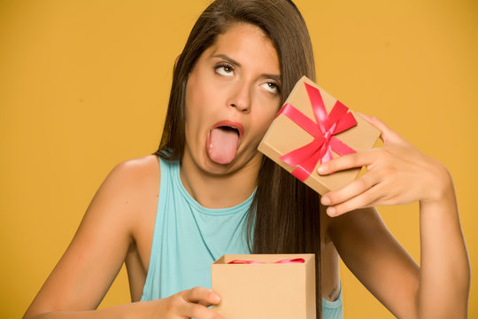Young disappointed woman opening a present box on yellow background
