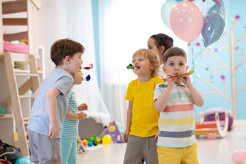 Children birthday party. Kids play and blow noisemaker horns