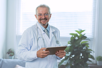 A cheerful mature doctor with a tablet in hands smiling at the camera, healthcare, and medicine
