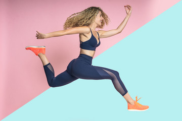 Beautiful runner woman and blonde athlete with curly hair performs exercise jumping in the air on isolated background wearing sportswear smiling and happy to have a healthy lifestyle and fitness