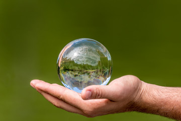 Glass ball with mirrored lake, trees and sky, lies in one hand against green background