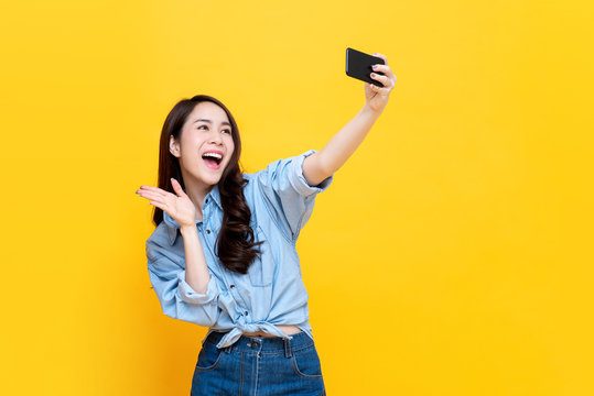 Asian woman taking selfie isolaed on yellow background