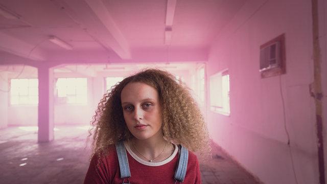 Portrait of teenage girl in empty, pink industrial building