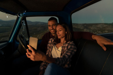 Young couple on a road trip taking a selfie in their car at dusk