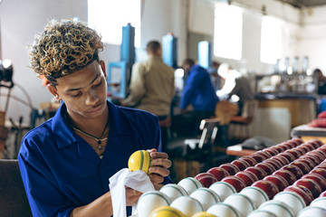 Young man working in sports equipment factory