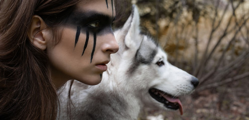 Close-up portrait of a woman hunter with war paint on her cheeks against the backdrop of a wolf face Wall mural