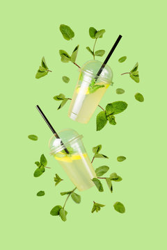Flying refreshing lemonade from a plastic cups with flying mint leaves on a green background. Jar full of cold cocktail. Fresh concept. Mock up.