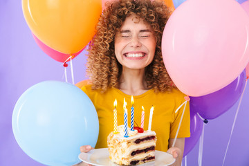 Image of joyful young woman celebrating birthday with multicolored air balloons and piece of cake