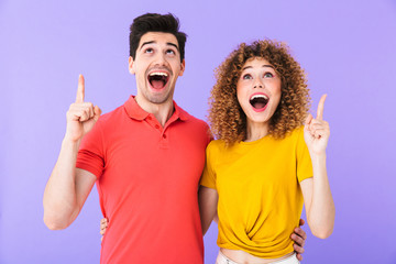 Portrait of amazed caucasian people man and woman in basic clothing smiling and pointing fingers upward at copyspace