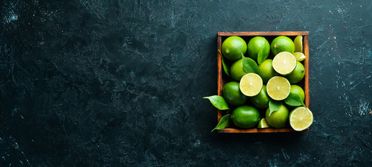 Green lime in a wooden box. Citrus fruits. On a black stone background. Top view. Free space for your text.