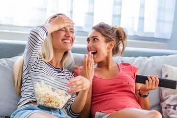 Portrait of funny and happy young women watching comedy in bed and laughing. Cheerful friends...