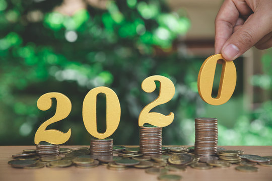 Growth of coins stack on wood blocks number 2020. 2020 NEW YEAR Business and saving money concept.