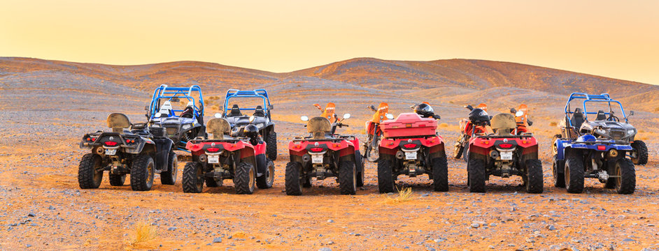 A group of riderless ATVs and motorbikes lined up in the Sahara desert