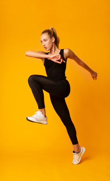 Woman Jumping Exercising On Yellow Background In Studio