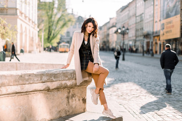 Attractive modern woman standing on the city street. Wall mural
