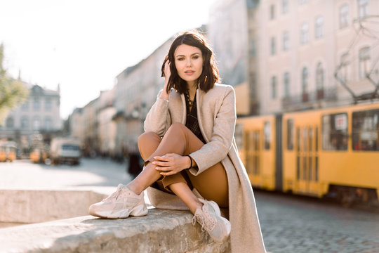 Beautiful young brunette woman in beige coat and brown pants posing in the center of the Old Town, standing near the stone monument. Ancient buildings, morning city background
