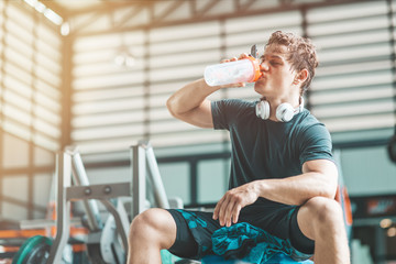 Portait of tired athletic man relaxing and drinking pre-workout drink from a classic fitness...