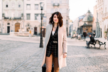 Pretty young woman with short dark hair in casual stylish clothes traveling with a wheeled suitcase, walking at the street of old European city Wall mural