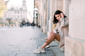 Outdoor portrait of a young beautiful fashionable lady sitting on stairs of old building on a street of the old city. Model wearing stylish clothes. Female fashion concept. City lifestyle. Wall mural