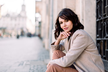 Portrait of young beautiful lady in brown pants and beige coat sitting on the stone stairs near the old building in city. City lifestyle. Copy space for text. Wall mural