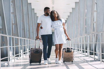 Loving black couple walking at covered passage in airport